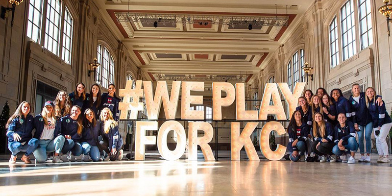 """Kansas City NWSL Team surrounding a """"We Play for KC"""" sign"""