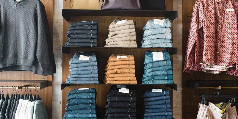Shelves at ULAH filled with jeans and button-down shirts